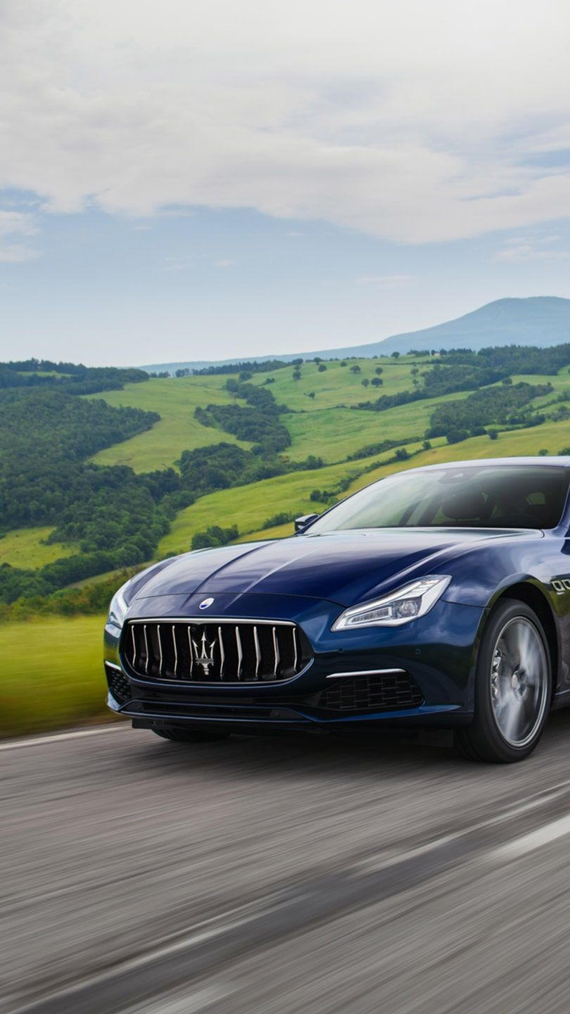 Maserati Quattroporte on the road - green hills on the background